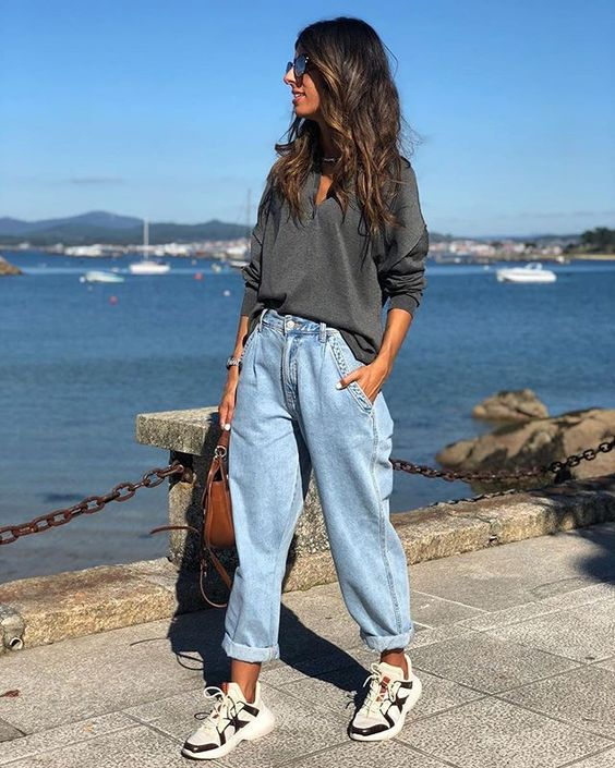 a grey oversized shirt, blue slouchy jeans, two tone trainers and a brown bag