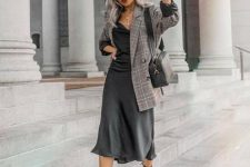 a grey slip dress, an oversized grey plaid blazer, a black bag and black square toe boots