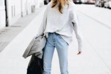 a grey sweater, light blue straight jeans, white booties, a grey coat and a black bag