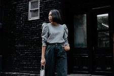 a grey top with puff sleeves, black slouchy jeans, black spikes booties and a small bag with fringe