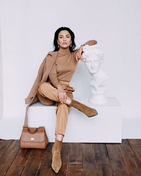 a monochromatic look with a tan turtleneck, gold pants, ocher booties, a tan light coat and an amber bag