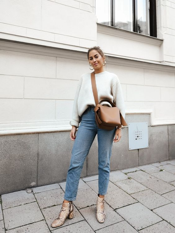 a neutral oversized sweater, blue straight leg jeans, snake print booties and a camel bag