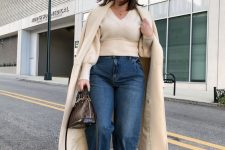 a neutral sweater with a V-neckline, blue slouchy jeans, black booties and a printed bag