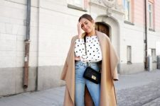a polka dot blouse, blue straight leg jeans, brown suede booties and a camel coat plus a black crossbody