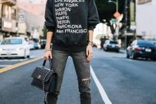 a printed sweatshirt, black ripped jeans, a black bag and burnt orange shiny booties