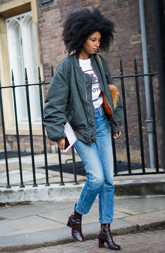a printed tee, blue jeans, printed boots, a graphite grey bomber jacket