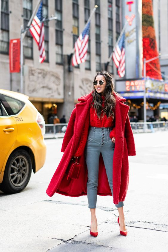a red blouse, blue high waisted jeans, red shoes, a fuchsia faux fur coat and a red bag