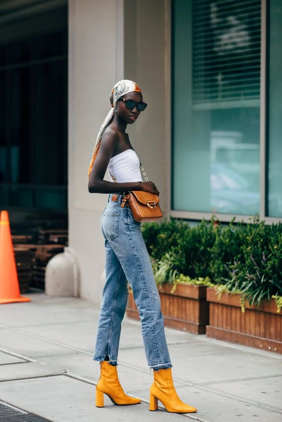 a strapless top, blue jeans, yellow ankle booties, a rust bag and a headband for a bold look