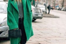 a striped top, black cropped jeans, black lacquer boots, an apple green oversized coat and a hunter green elegant bag