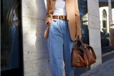 a stylish casual work look with a white top, blue slouchy jeans, white shoes, a tan oversized blazer and a brown bag