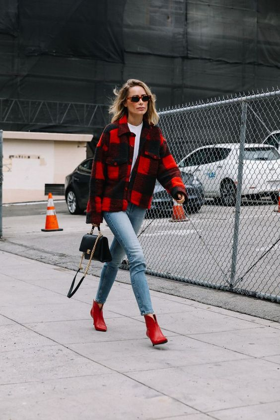 a stylish outfit with a white tee, blue jeans, red booties, a black and red shirt jacket and a black bag