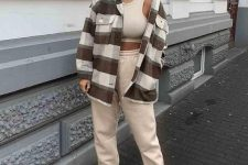 a stylish sporty look with a tan crop top and joggers, white trainers, a plaid shirt jacket