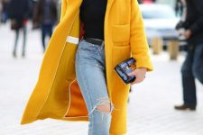 a super chic look with a black turtleneck, blue ripped jeans, black ankle strap shoes and a sunny yellow faux fur coat