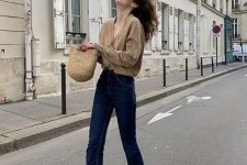 a tan cardigan tucked into navy jeans, tan suede booties and a woven bag for the fall