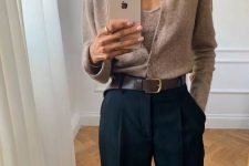 a tan knit top and a matching cardigan tucked into navy pants and a brown belt for a stylish look
