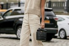 a tan knit vest, creamy jeans, black square toe heels and a black bag of a creative shape
