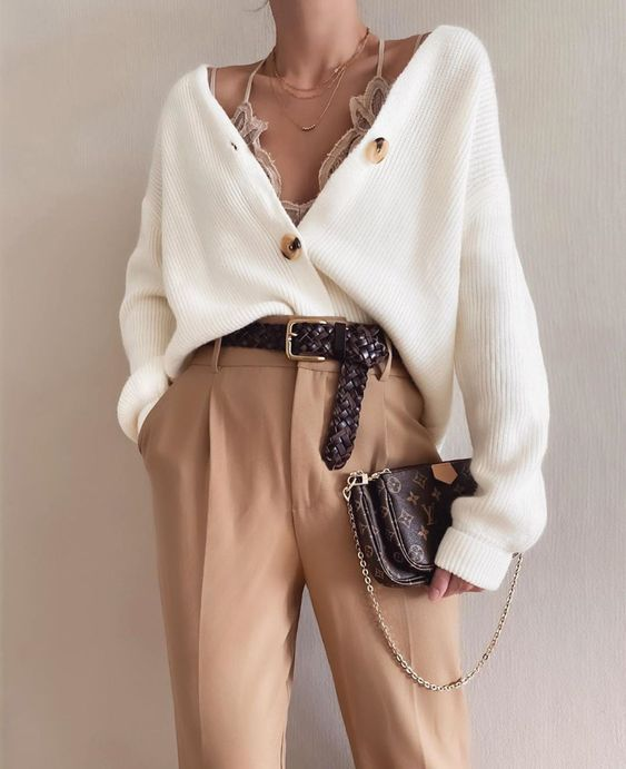 a work look with a cardigan, a tan lace bralette, a white cardigan tucked into tan pants, a brown belt and a bag