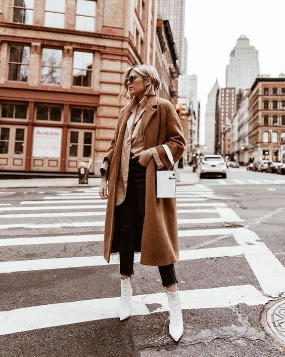 a tan oversized shirt, black skinnies, white pointed toe boots, a camel coat and a white bucket bag