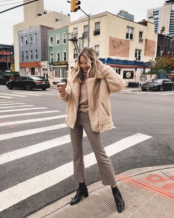 a tan turtleneck, plaid cropped pants, black ankle booties, a neutral faux fur short coat