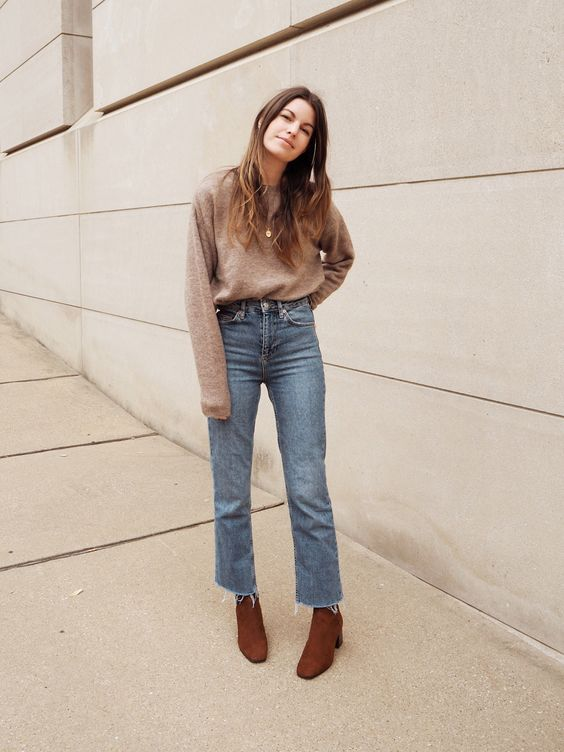 a taupe sweater, light blue straight jeans with a raw hem, rust-colored booties and layered necklaces