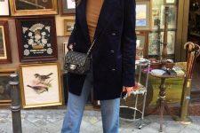 a taupe turtleneck, light blue jeans, a navy velvet blazer, a black bag and black lace up booties