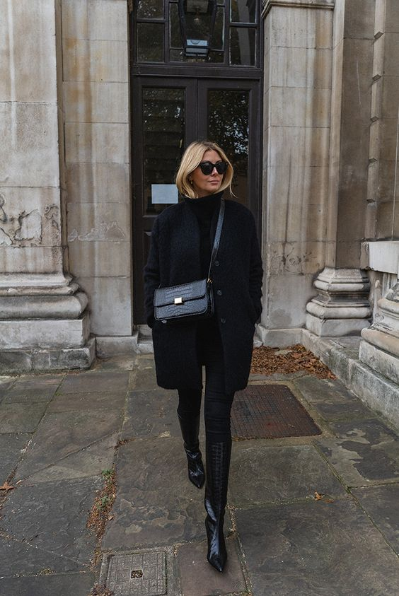 a total black look with a turtleneck, skinnies, black knee boots, a coat, a bag
