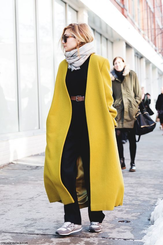 a total black outfit with grey trainers, a grey scarf and a mustard midi coat for a bold touch