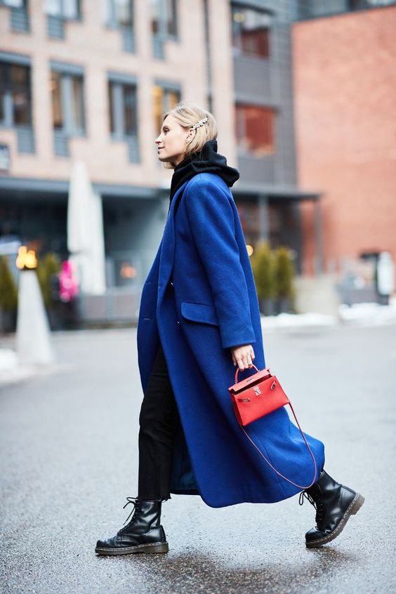 a trendy fall look with a black hoodie, black jeans, black combat boots, an electric blue coat and a red mini bag