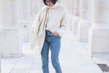a white chunky knit sweater, blue jeans, purple suede booties and a creamy bomber jacket