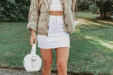 a white crop top, a white denim mini skirt, a tan quilted jacket, white booties and a white round bag
