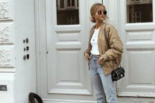 a white cropped top, blue jeans, a tan bomber jacket, fur mules and a black crossbody bag