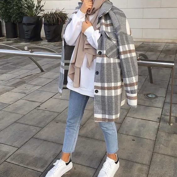 a white hoodie, blue jeans, white sneakers, a grey plaid shirt jacket and a tan scarf