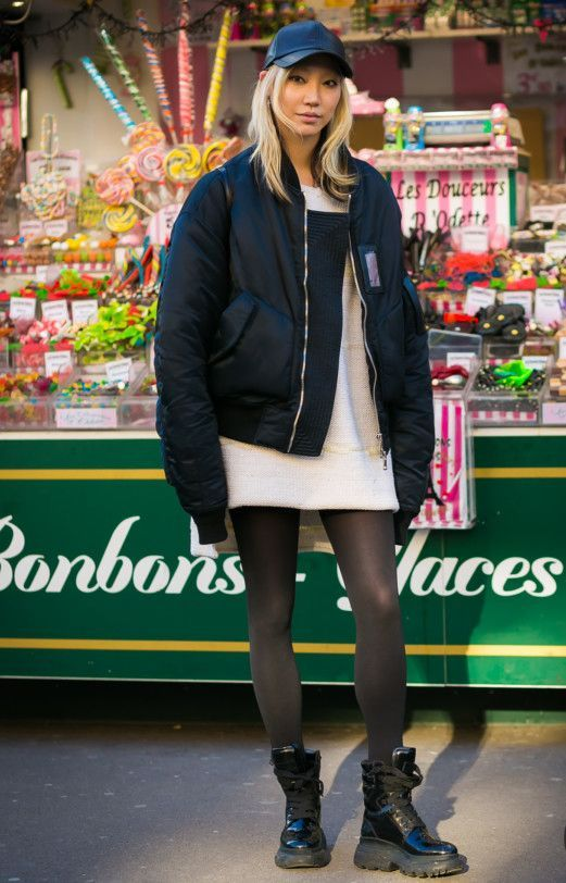 a white knit mini dress, black tights, black combat boots and a black bomber jacket plus a cap