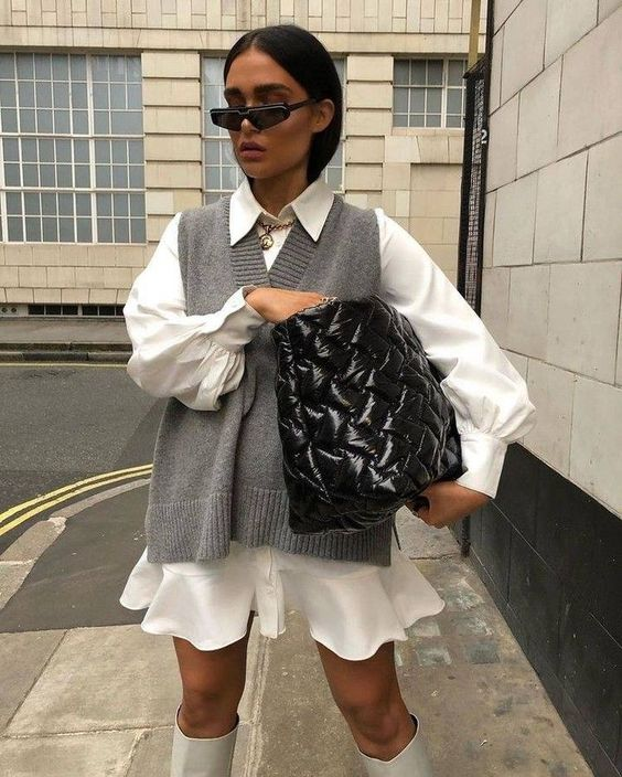 a white mini shirtdress with long sleeves, a grey knit vest, creamy boots and a black bag for a fashion-forward girl