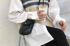 a white oversized shirt, a striped oversized knit vest and black skinnies plus a small bag