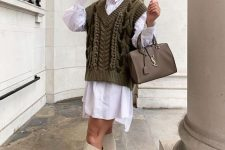 a white oversized shirtdress, an olive green knit vest, creamy boots and a grey bag
