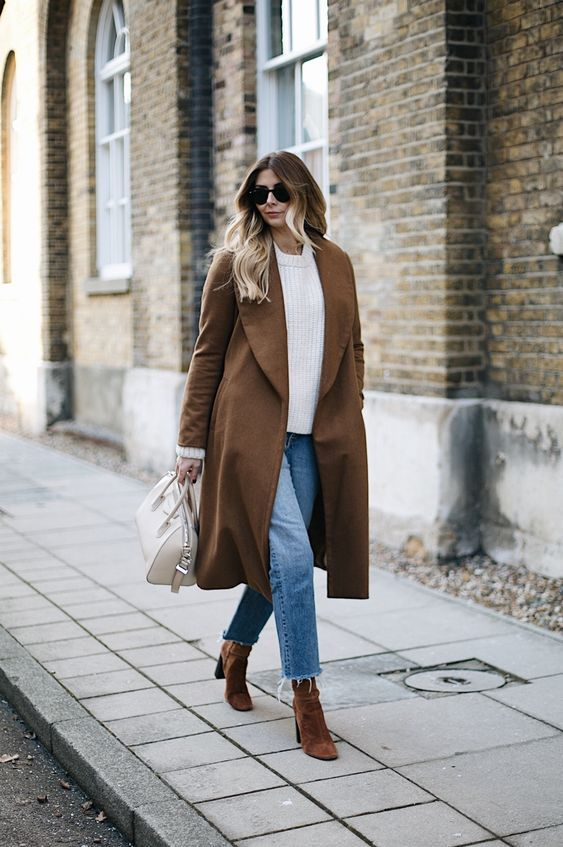 a white oversized sweater, light blue jeans with a raw hem, rust-colored velvet booties and a brown trench