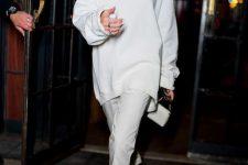 a white oversized sweatshirt, skinny pants, white semi sheer shoes and a mini bag