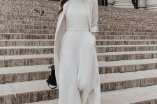 a white plain jumper with culotte pants, a white trench, sneakers and a black bag