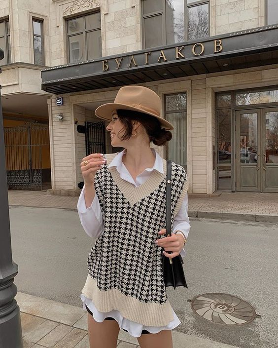 a white shirt, a printed knit vest, black shorts and a hat plus a bag to wear right now