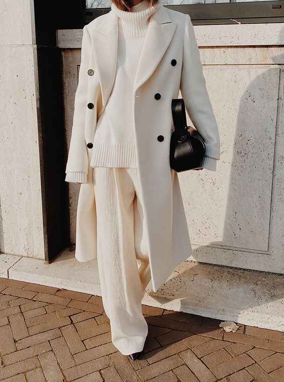 a white sweater, white pants, a white coat with black buttons and a black bag plus black booties