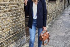 a white t-shirt, blue raw hem jeans, a navy blazer, a tan bag and tan velvet booties for the fall