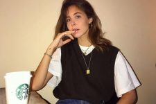a white tee, a black knit vest, blue jeans and layered necklaces for a relaxed 90s inspired look