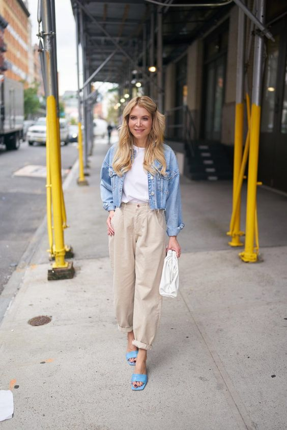 a white tee, a blue denim jacket, tan slouchy jeans, blue heeled mules and a white clutch