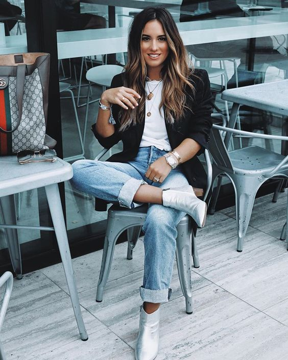 a white tee, blue jeans, a black blazer, silver ankle booties and a printed tote