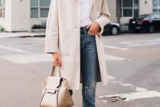 a white tee, blue ripped jeans, white pointed toe boots, a creamy coat and a nude bag