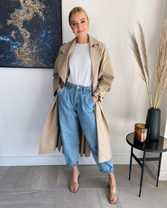 a white tee, blue slouchy jeans, tan heeled mules, a tan trench for a comfy and chic fall outfit