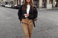 a white tee, tan pants, a black leather jacket, brown boots and a backspack for the fall