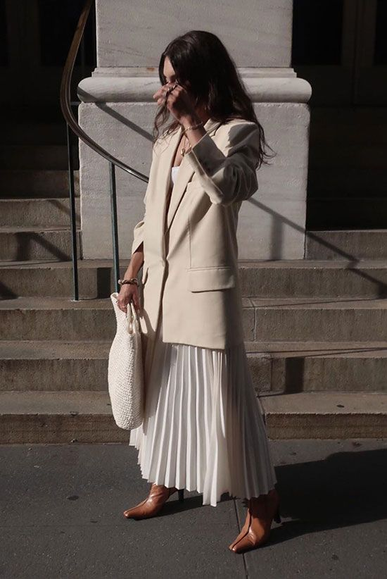 a white top, a white pleated midi skirt, an oversized creamy blazer, brown square toe boots and a white woven bag