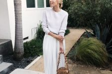 a white top, a white pleated midi skirt, tan flats and a wooden bag with a beaded handle